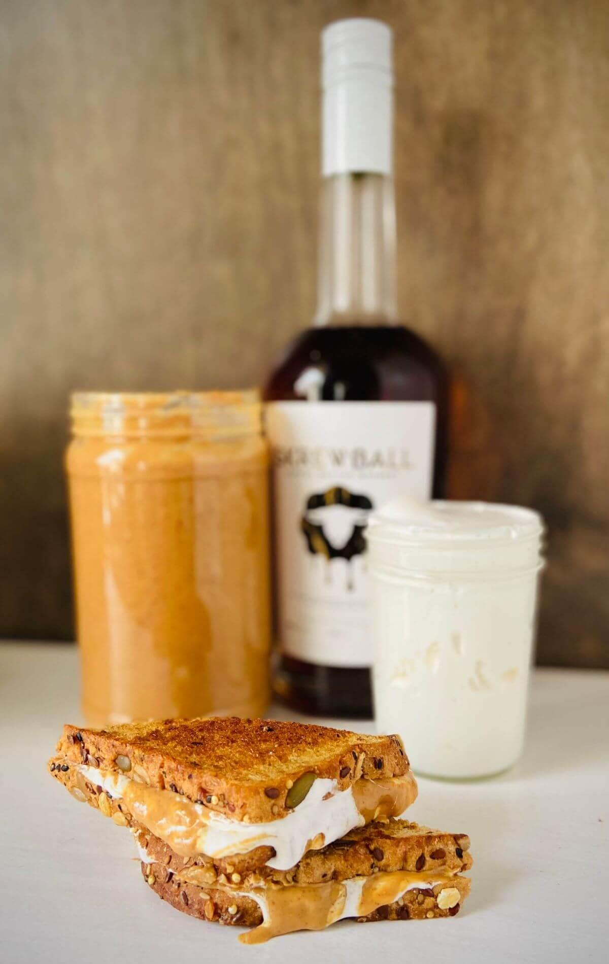 Grilled fluffernutter sandwich with a jar of peanut butter, marshmallow fluff, and peanut butter whiskey