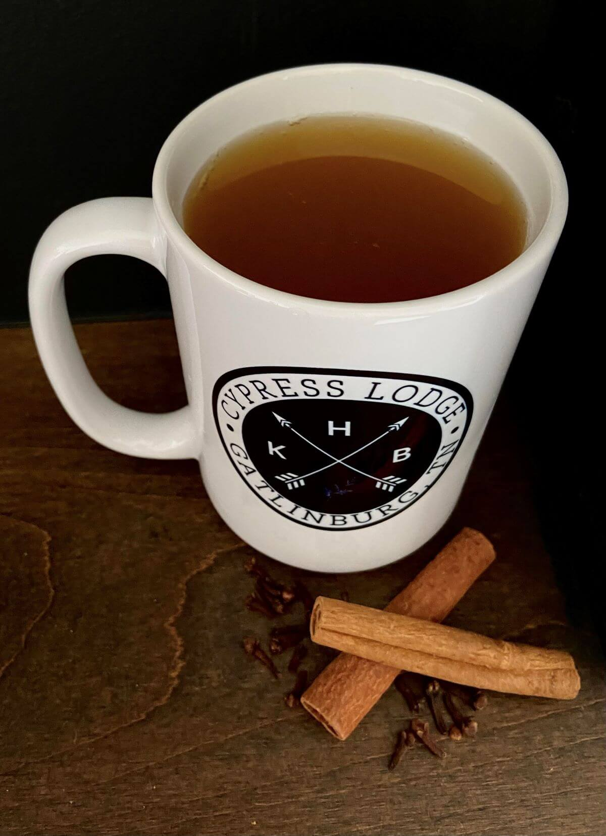 KHB Cypress Lodge Mug filled with warm peanut butter whiskey apple cider, a few cinnamon sticks and spices laying on the table beside the mug
