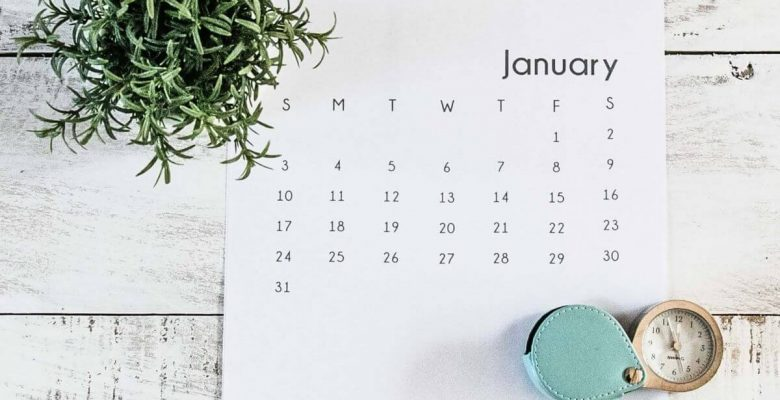 Monthly calendar laying on a table open to january