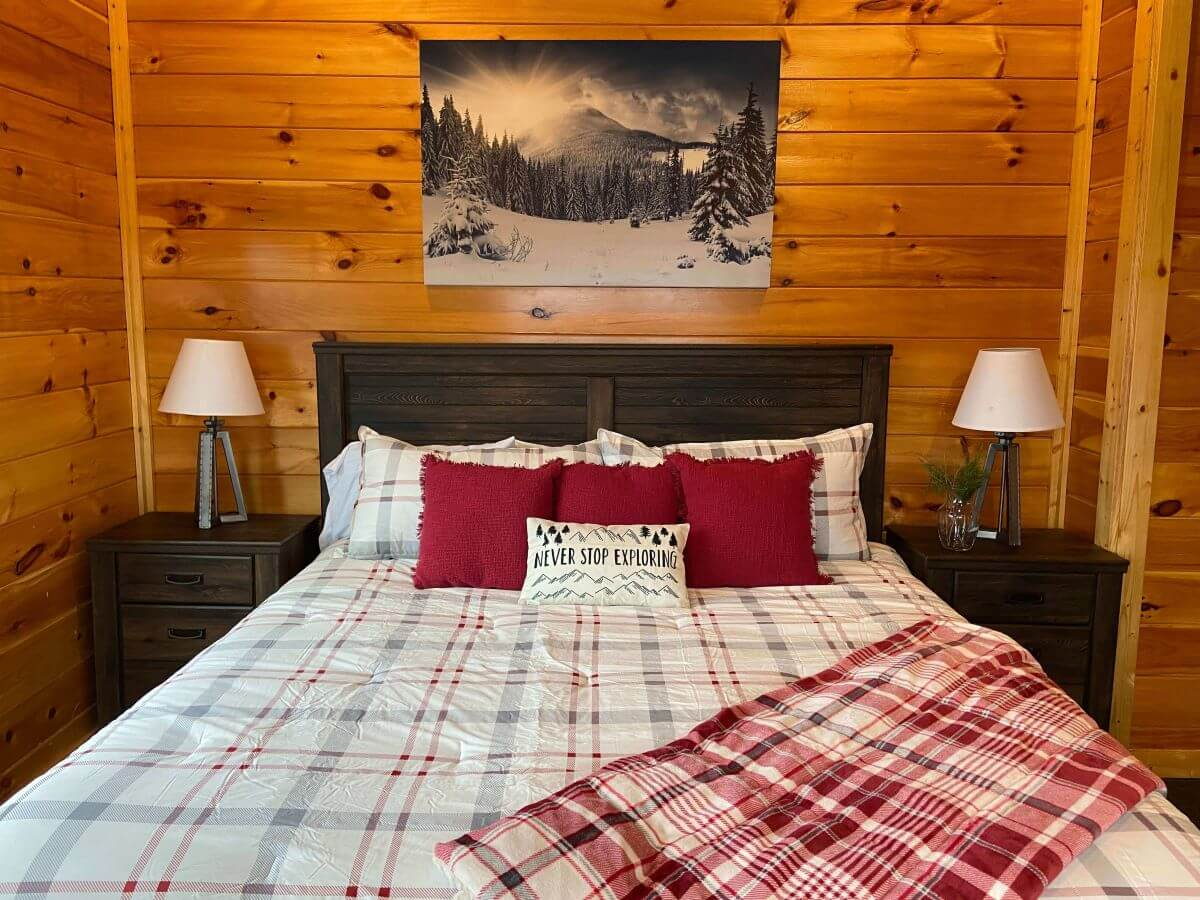 Cypress Lodge Bedroom with king sized bed, gray and red plaid bedspread, blanket, and red pillows