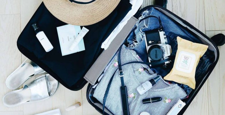 Open packed suitcase lying on the ground