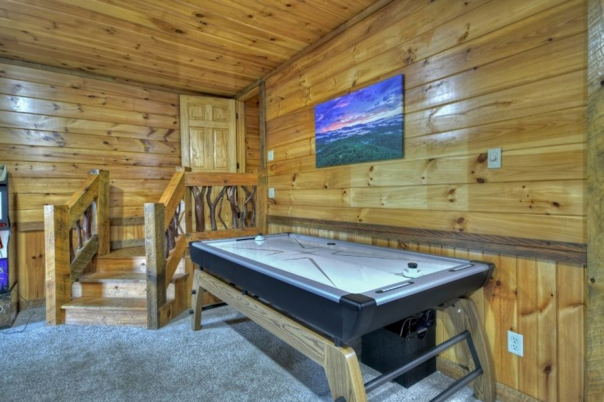 Choctaw Mtn Lodge basement air hockey table with mountain canvas on the wall