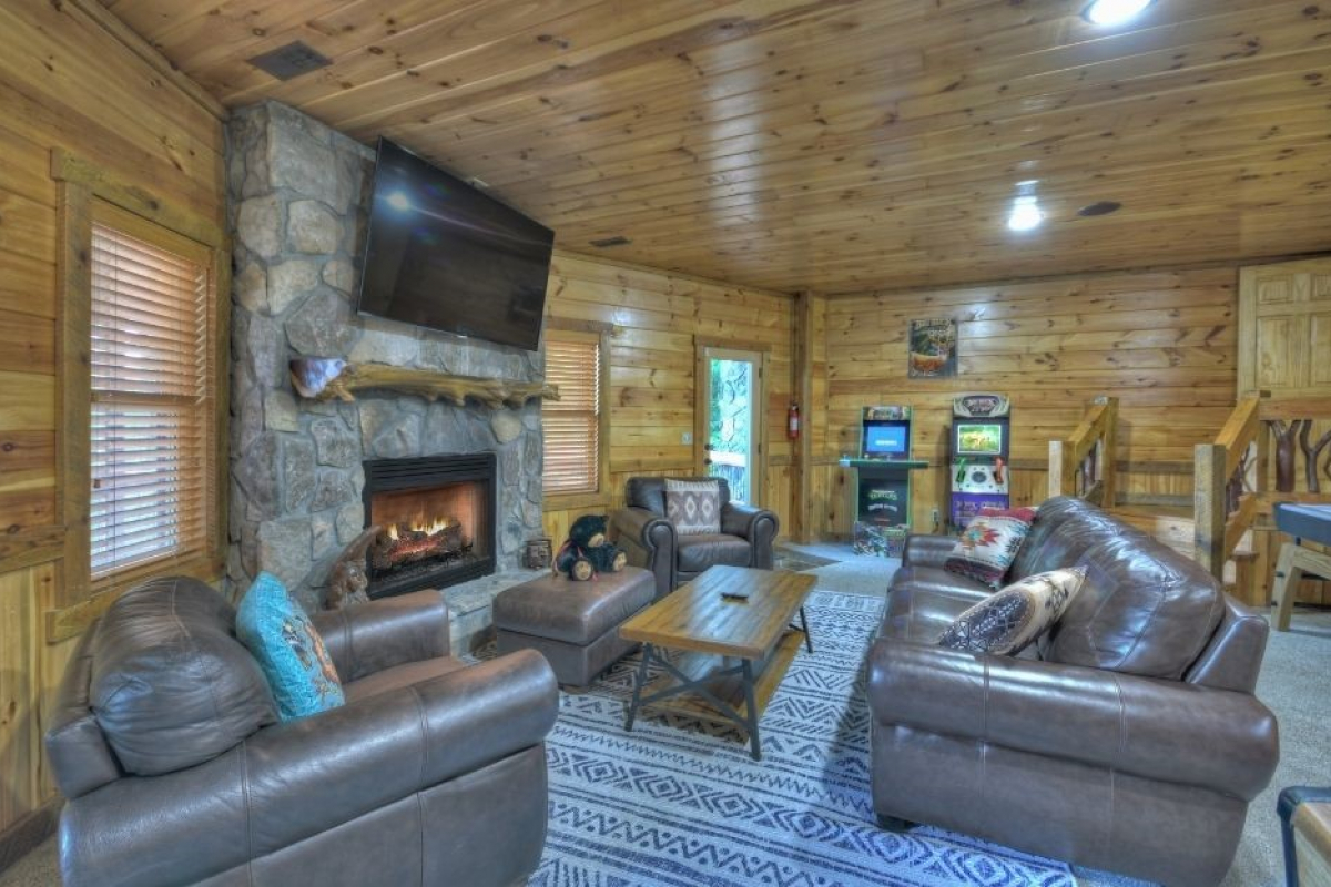 """Choctaw Mtn Lodge basement seating in front of 65"""" TV and fireplace with arcade games in the background"""