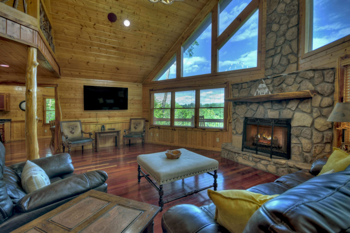 """Choctaw Mtn Lodge Living room with couch, chairs, fireplace,and 65"""" TV and prowl front windows with a view"""