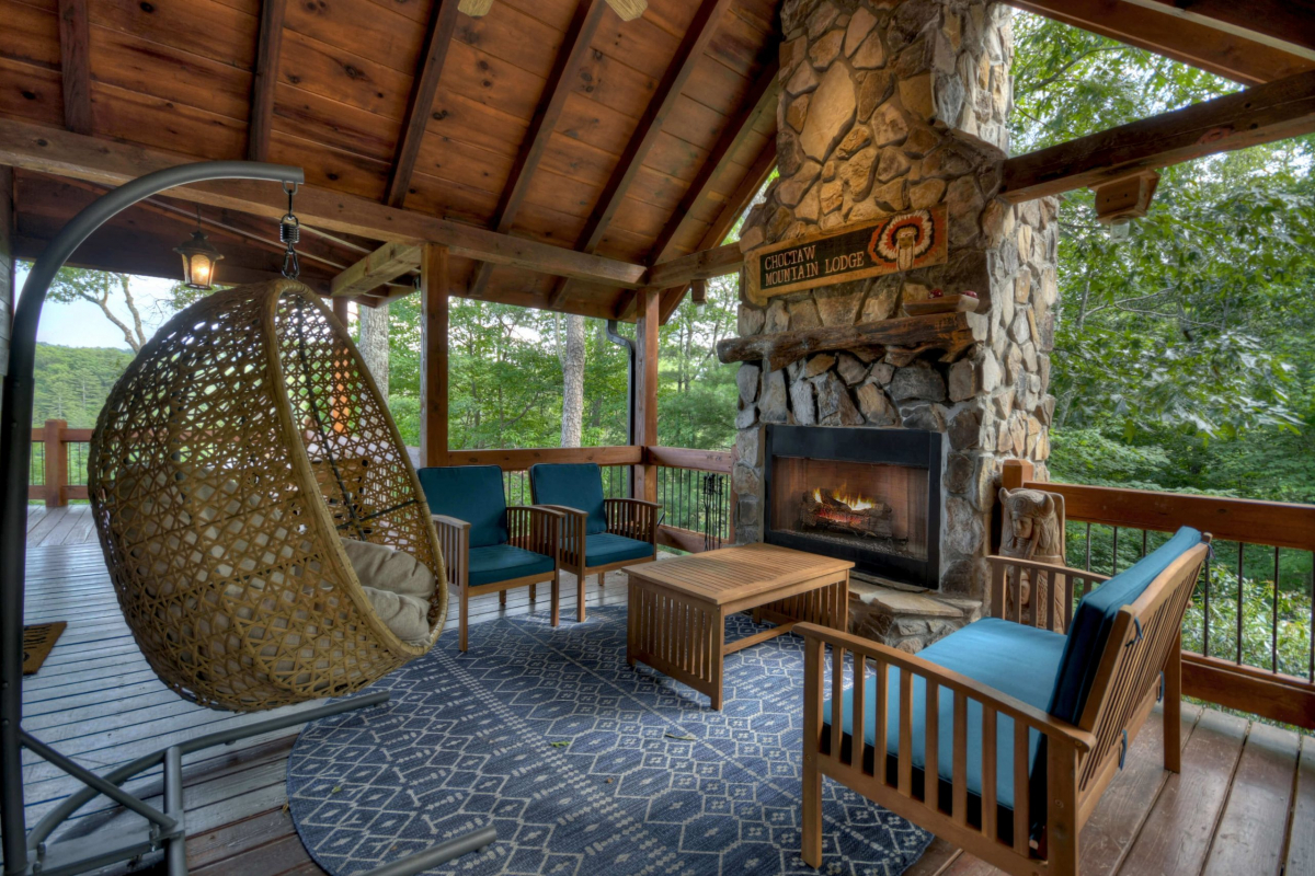 Choctaw Mtn Lodge outdoor fireplace with seating area and egg chair