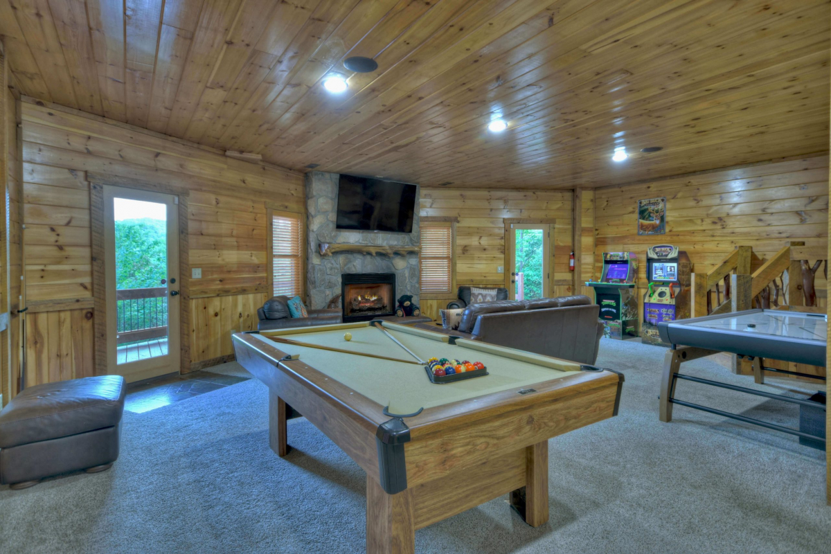 """Choctaw Mtn Lodge basement with pool table, 65"""" TV with couch and chairs, arcade games, air hockey table"""