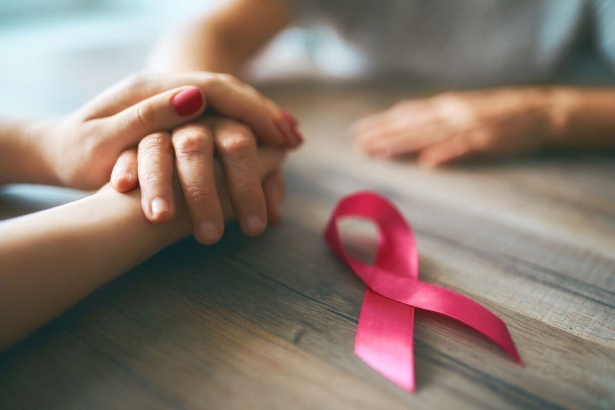 two people holding hands across a table with a pink breast cancer ribbon laying next to their hands